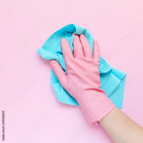 Fotomural Employee hand in rubber protective glove with micro fiber cloth wiping wall from dust