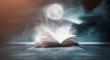 canvas print picture An open book on a wooden table under the night sky against a dark forest. Magical radiance. Night scene.
