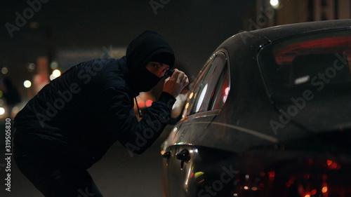 Photo Robber man checking breaking entering alarm shines a flashlight in a car stealin