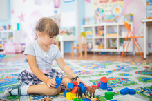 Little Girl Playing. Kids With Stuffed Animal Toys. Children Sit On A Children Rug In A Play Room At Home Or Kindergarten