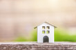 Miniature white toy model house in wooden background near green backdrop. Eco Village, abstract environmental background. Real estate mortgage property insurance dream home ecology concept
