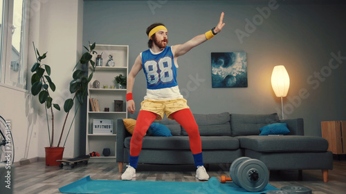 Attractive funny guy in retro sports costume dancing and warming up before hard training.