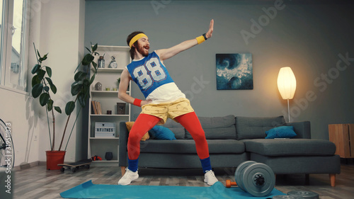 Funny stupid-looking reto fitness man dancing enjoying music and warming up on workout in the living room Canvas