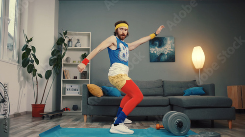 Tela Stupid-looking funny athlete man in retro outfit dancing and warming up having an intense home workout