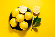 Fresh Ripe Lemons On The Plate On Bright Yellow Background With Copy Space For Your Text.