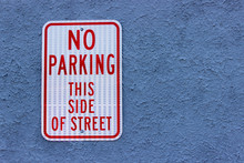A No Parking Sign In Red Letters Attached To A Blue Wall.