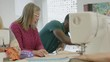 Mature students cutting sewing pattern and talking in classroom