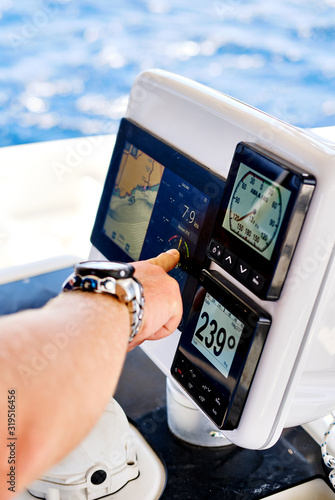 Foto Close up male hand pointing on navigation devices in catamaran deck, adventure r