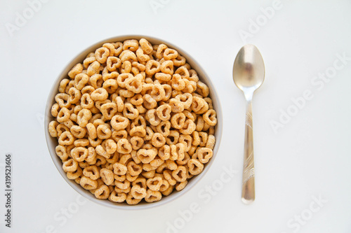 Bowl of whole grain oat cereal with a silver spoon on a white background , back view Canvas Print