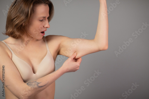 Fotografia, Obraz Chubby Woman Pinching Upper Arm Fat Isolated on Grey Background