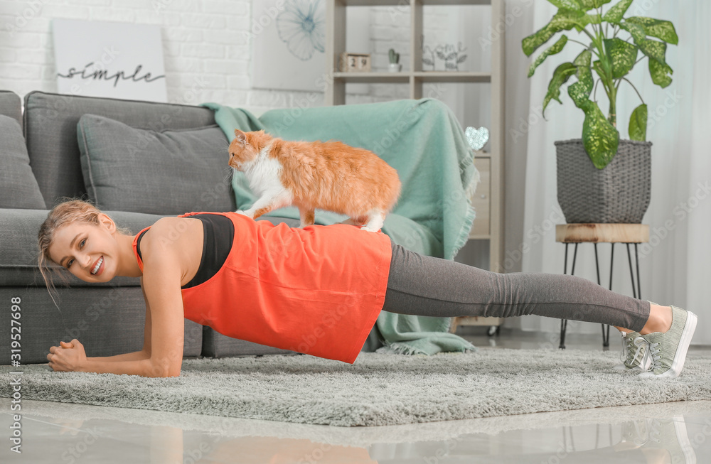 Fototapeta Young woman with cute cat practicing yoga at home