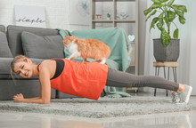 Young Woman With Cute Cat Practicing Yoga At Home