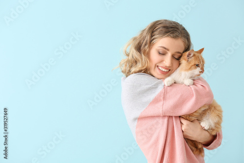 Beautiful young woman with cute cat on color background Slika na platnu