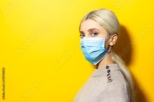 Fotografie, Obraz Studio profile portrait of young blonde girl wearing medical flu mask and sweater on yellow background with copy space