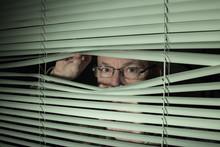 Man Peeking Through Blinds