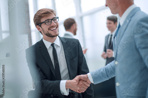 smiling businessman shaking hands with his business partner