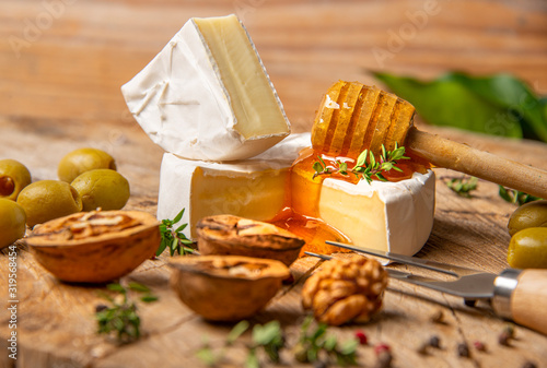 obraz PCV cheese and honey on old wooden table