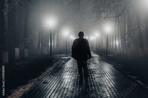 Sad man alone walking along the alley in night foggy park Fototapeta
