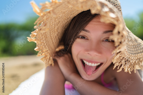 Cuadros en Lienzo Happy funny face Asian young woman doing goofy facial expression sticking tongue out on summer vacation relax holiday sun tanning on beach having fun