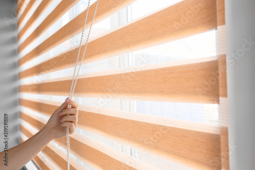 Woman opening blinds on window Wallpaper Mural