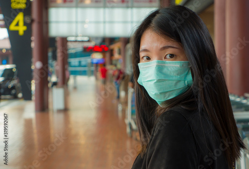 Fototapeta young beautiful and attractive Asian Chinese student at airport wearing protective facial mask against China Coronavirus epidemic outbreak spreading breathing syndrome obraz