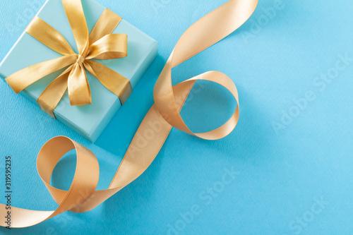 Photo 青いギフトボックスと金色のリボンのプレゼントのイメージ