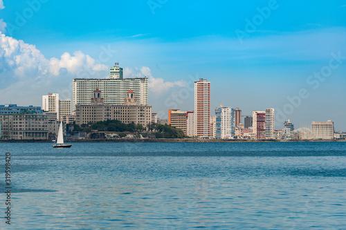 Fotomural SEA BY BUILDINGS AGAINST SKY IN CITY