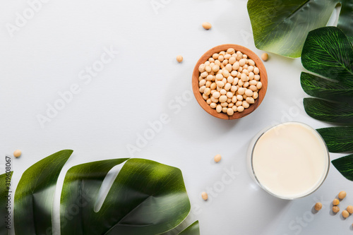 Fototapeta Soy milk and soy bean on gray table kitchen background. Non-dairy milk concept. Vegan drink. Hard light. Copy space obraz