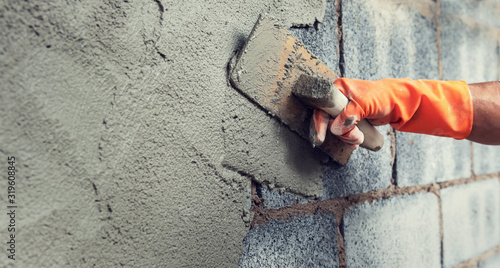 Fototapeta close up hand worker plastering cement on wall for building house obraz