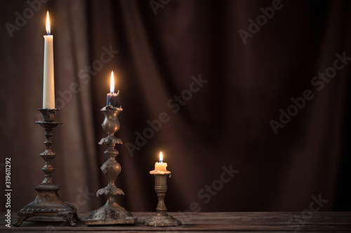 Leinwand Poster antique candlestick with burning candle on old wooden table on background brown