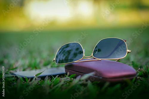 Obraz Close-Up Of Sunglasses On Field - fototapety do salonu
