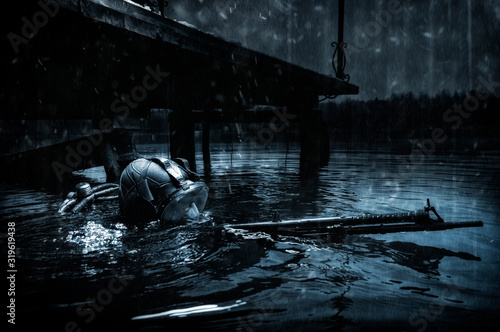 Military diver emerges from under the water and takes aim from the machine gun Canvas Print
