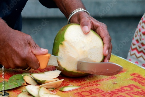 Tela Midsection Of Man Cutting Coconut On Table