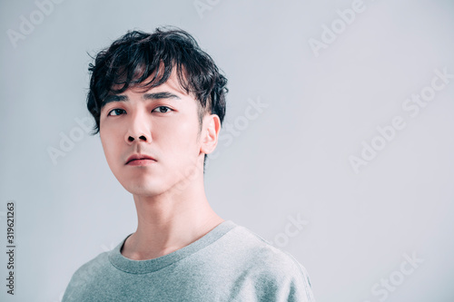 young asian handsome man isolated on gray background