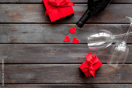 Fototapeta Valentines Day concept with wine, glasses, red present box on dark wooden background top-down copy space obraz