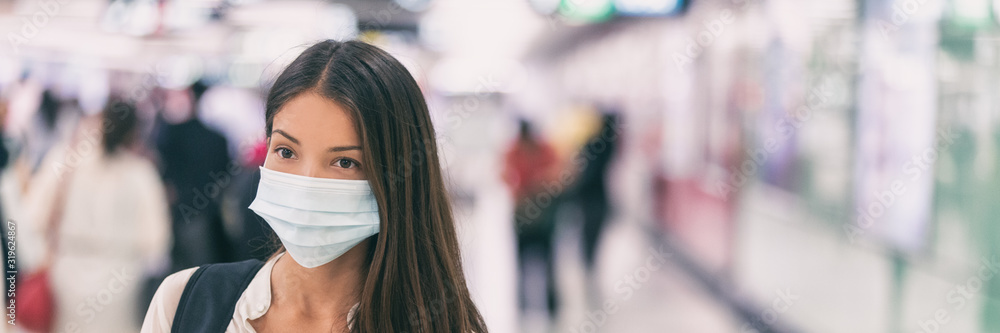 Fototapeta Coronavirus corona virus Asian woman wearing flu mask walking on work commute in public space transport train station or airport panoramic banner.