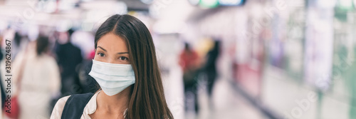 Coronavirus corona virus Asian woman wearing flu mask walking on work commute in public space transport train station or airport panoramic banner. - 319624867