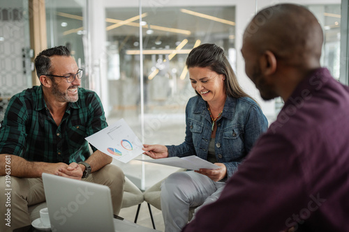 Happy smiling successful business colleagues having a candid seated casual meeting