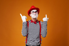Mime In Red Hat And Vest Showing Thumb Up On Orange Background