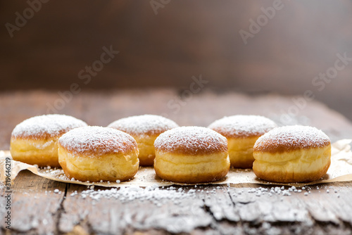 Fototapeta Close-up of donuts (Berlin pancakes) dusted with powdered sugar served on a rustic wooden table obraz