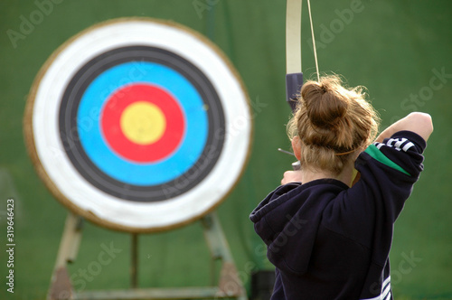 Valokuva Rear view of girl aiming at target with bow and arrow