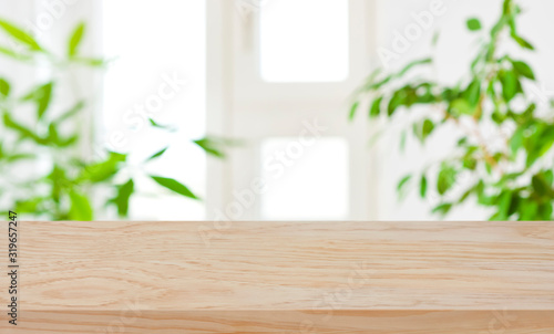 Obraz Wood table top on blur window and green plants background - fototapety do salonu