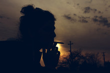 Silhouette Woman Smoking Cigarette During Sunset