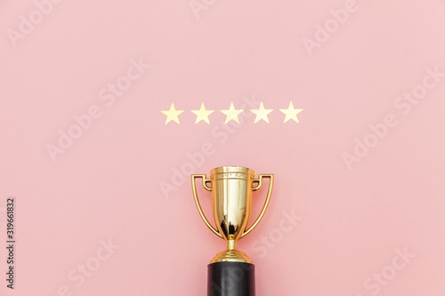 Cuadros en Lienzo Simply flat lay design winner or champion gold trophy cup and 5 stars rating isolated on pink pastel background