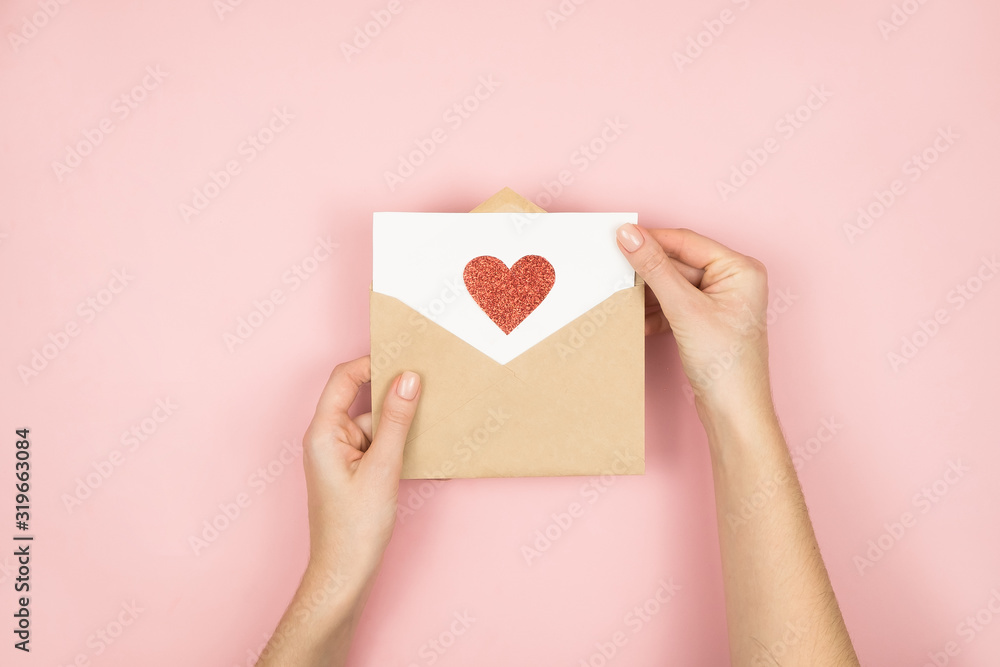 Fototapeta Love letter in women hands on Valentines Day. Handmade postcard with red heart on pink background. 14 February concept