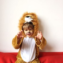 Portrait Of Boy Gesturing In Lion Costume While Sitting On Sofa