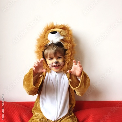 Fotomural Portrait Of Boy Gesturing In Lion Costume While Sitting On Sofa