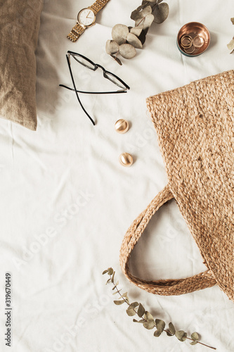 Fashion women accessories, straw bag, pillow, eucalyptus branches on white linen. Flat lay, top view fashion blogger concept for social media, website, blog. Wall mural