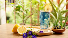 A Glasses Of Blue Butterfly Pea Flower Juice Drinking, Decoreted With Yellow Lemon Sliced And Fresh And Dry Asian Pigeon Wings Flowers, On Wooden Table And Green Blurry Background