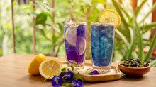 Two Glasses Of Blue And Violet Butterfly Pea Flower Juice Drinking, Decoreted With Yellow Lemon Sliced And Fresh And Dry Asian Pigeon Wings Flowers, On Wooden Table And Green Blurry Background